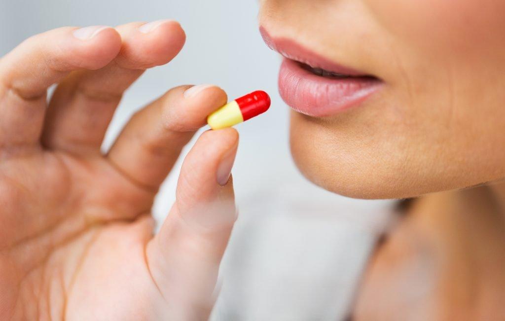 Женщина пьет таблетку